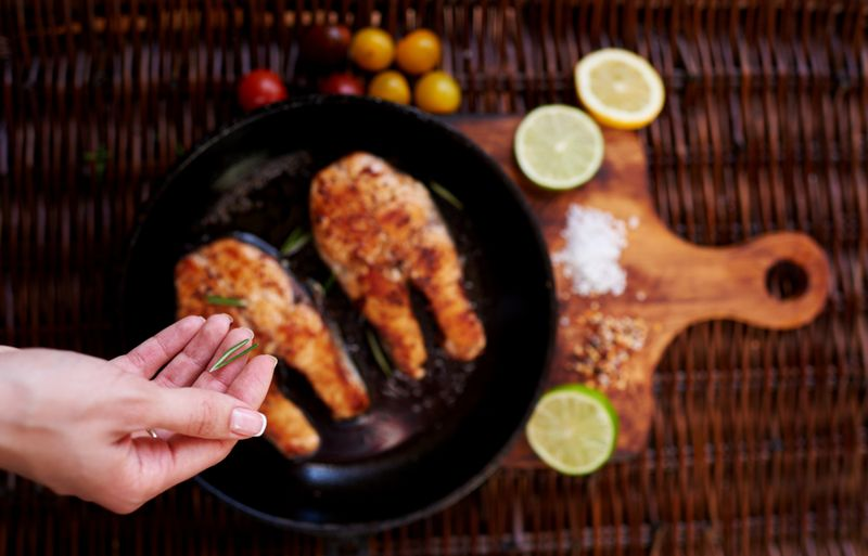 woman's hand sprinkling rosemary on grilled fish