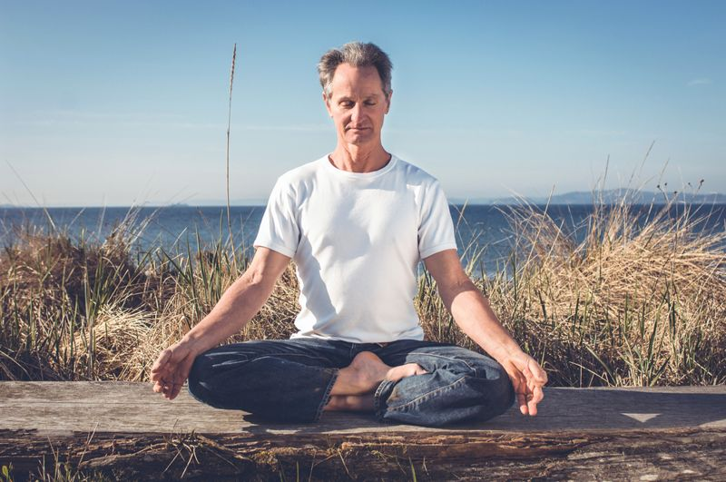 a middle aged man meditating by the beach