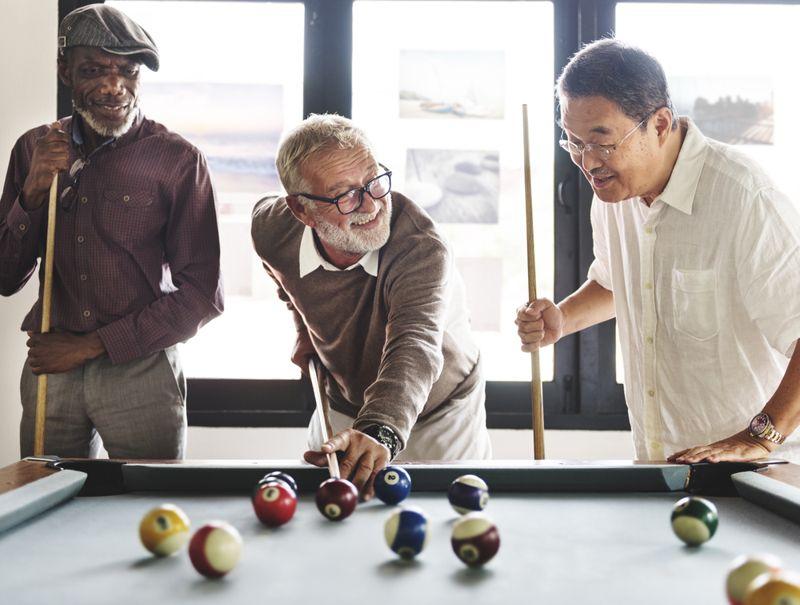 three older men playing pool and smiling