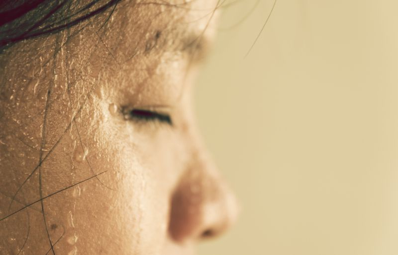 side profile of a woman's face, sweating for exercise