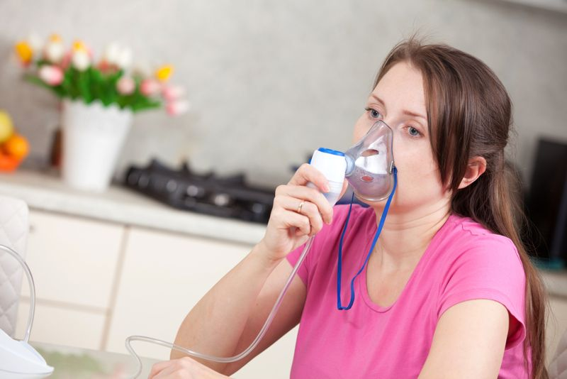 woman at home using a nebulizer breathing machine