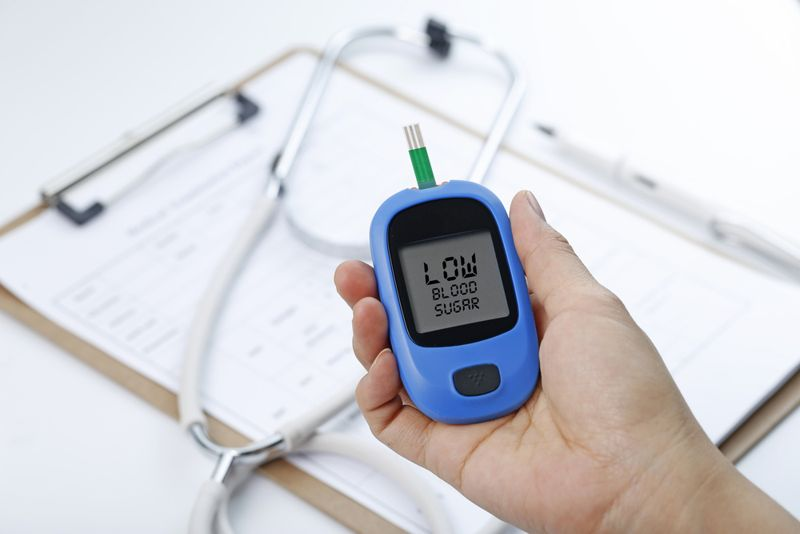 hand holding blood sugar device reading low blood sugar