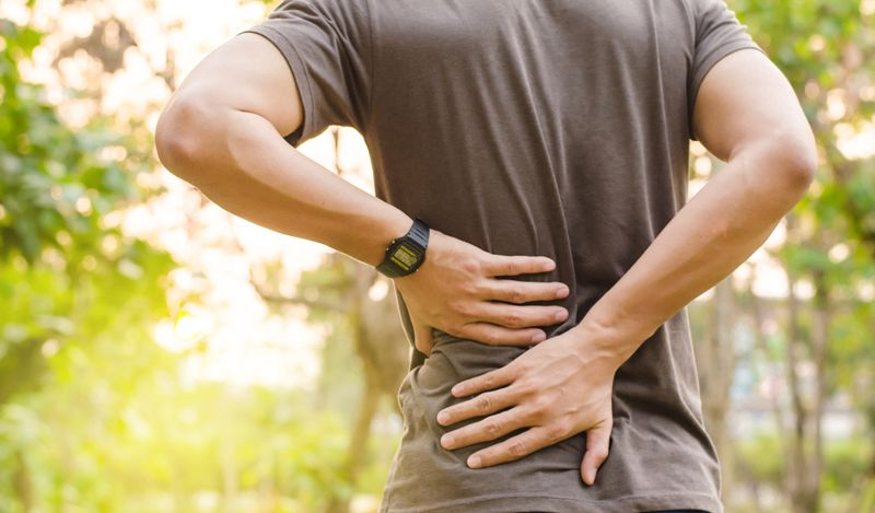 man outside experiencing lower back pain