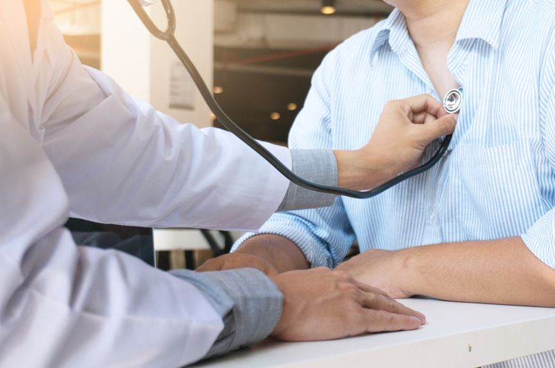 cropped image of doctor checking male patient's heart with stethoscope