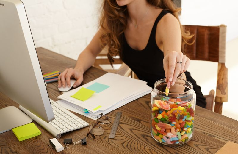 eating addiction concept woman on computer eating candy