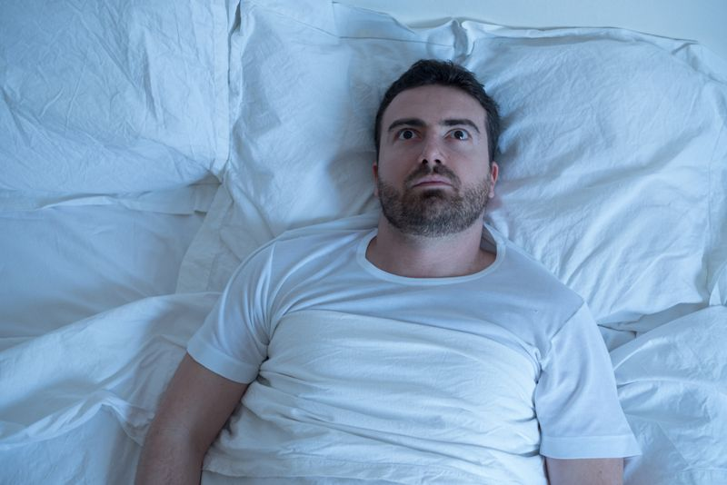 man in bed wide awake