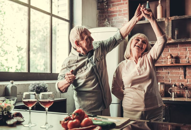 an older couple dancing in the kitchen