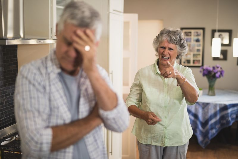 older angry woman yelling a husband in kitchen