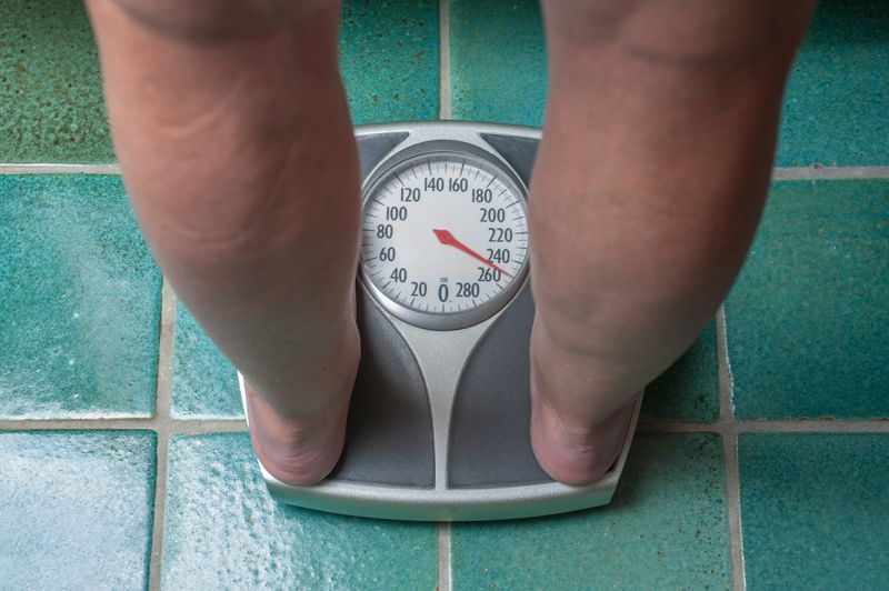 person who is overweight standing on bathroom scale