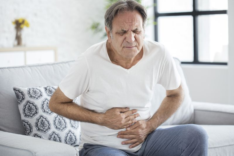 an older man experiencing abdominal pain