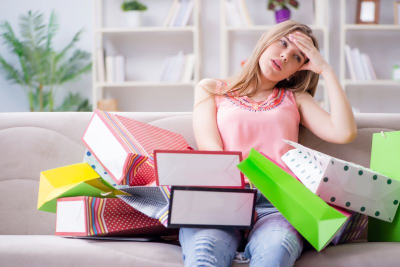 woman on couch looks exhausted surrounded by shopping bags