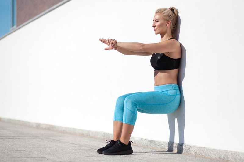 woman in fitness clothing doing a wall sit outside