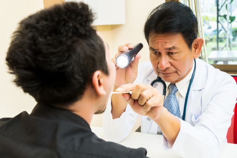 doctor inspecting patient's tongue