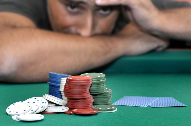cropped image of a stressed man with all his chips in the poker game
