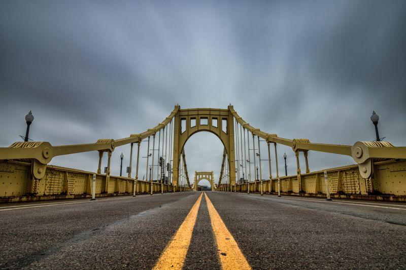 Grey clouds over a suspension bridge.