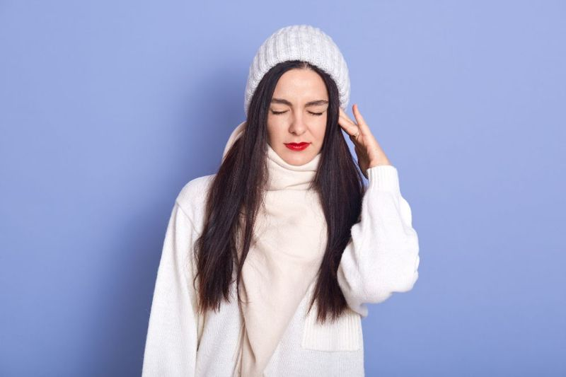 woman with an ear ache wearing a toque and sweater