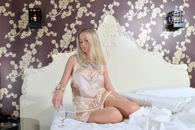 Fashion model on a bed in a slip dress