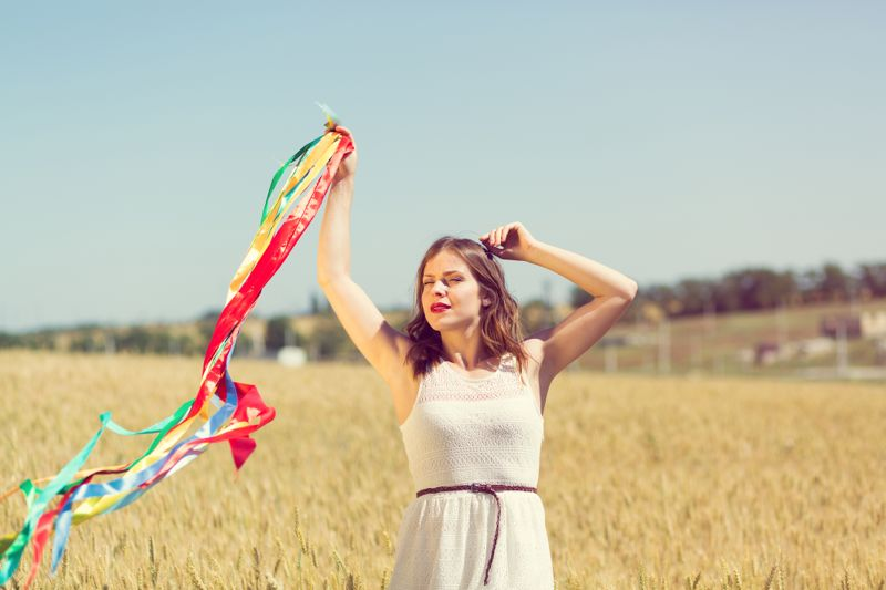 Happy girl holding colorful ribbons in the field