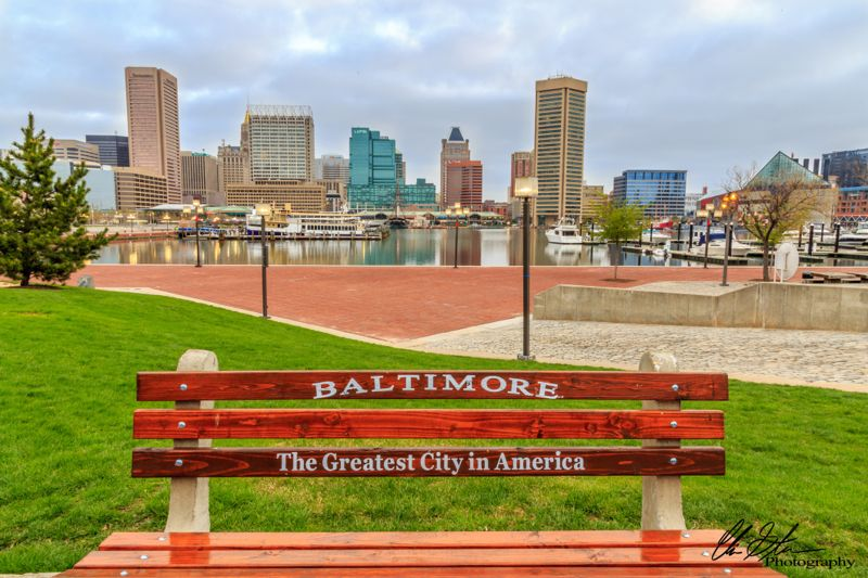 """A bench featuring the words, """"Baltimore, The Greatest City in America"""" near Baltimore's Inner Harbor."""