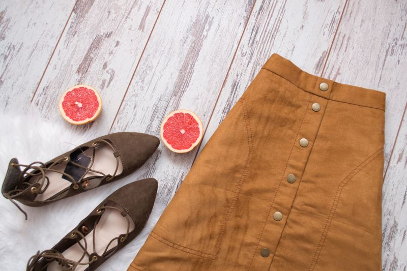 Brown suede skirt, brown suede shoes, cut grapefruit halves. Wooden background. Fashion concept. top view