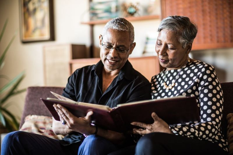 nostalgic older couple looking at photo albums