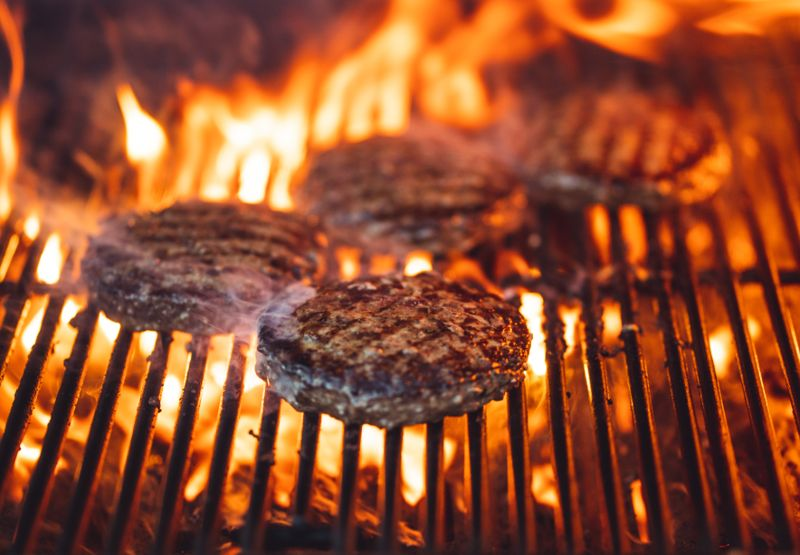 Burgers on an open grill flame