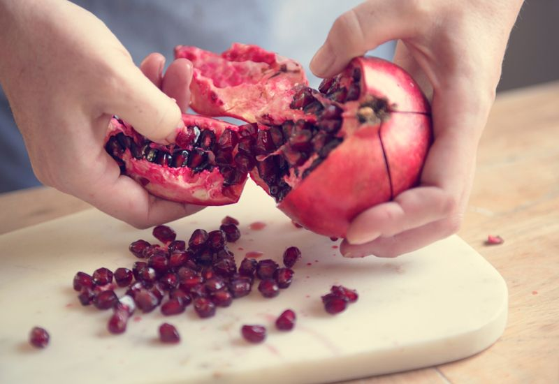 person breaking open a pomegranate over the counter