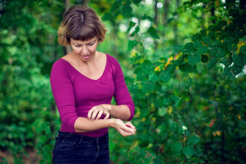 woman scratching her inner forearm, in nature