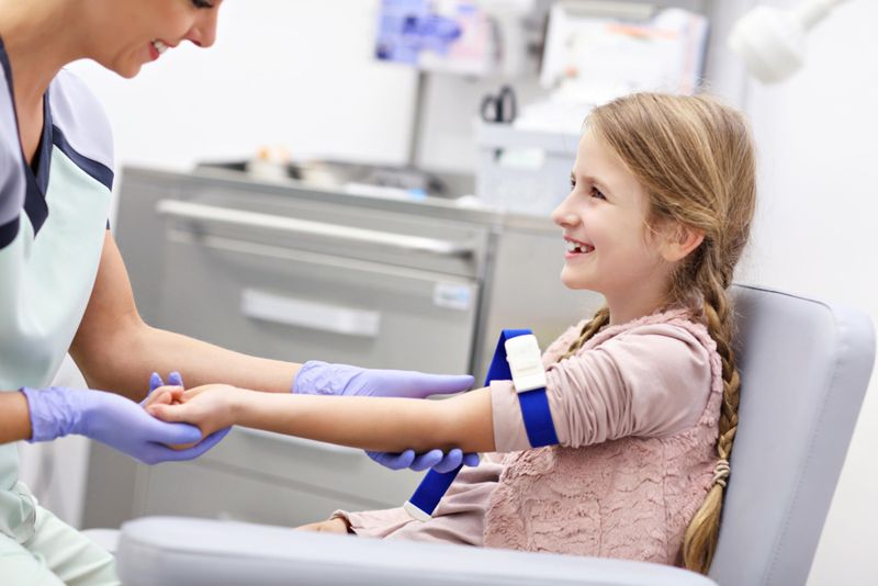little girl having blood taken at hospital