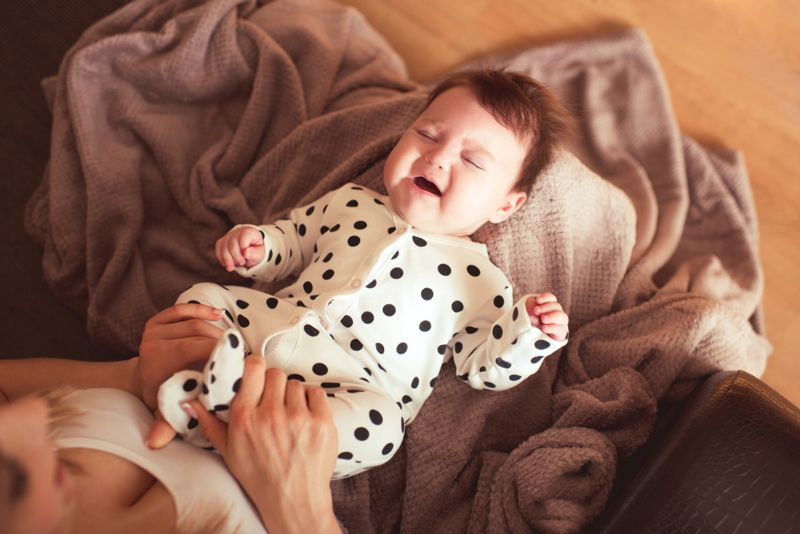baby crying in mother's lap