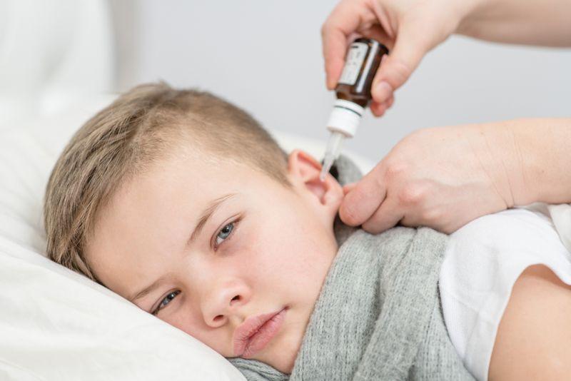 sick little boy getting ear drops