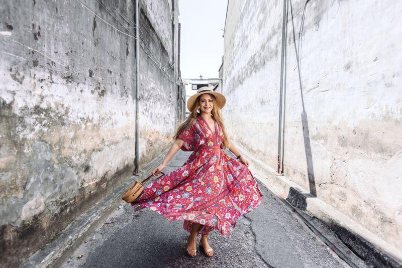 Boho girl in maxi dress and straw hat walking
