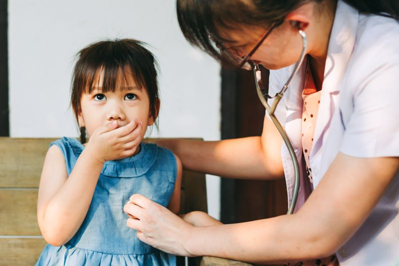 doctor checking headbeat and breathing of coughing child