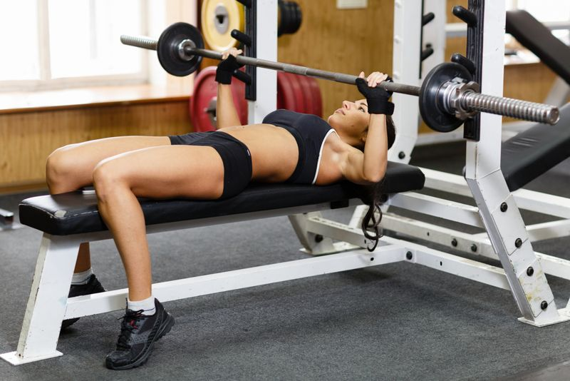 woman doing a bench press at the gym
