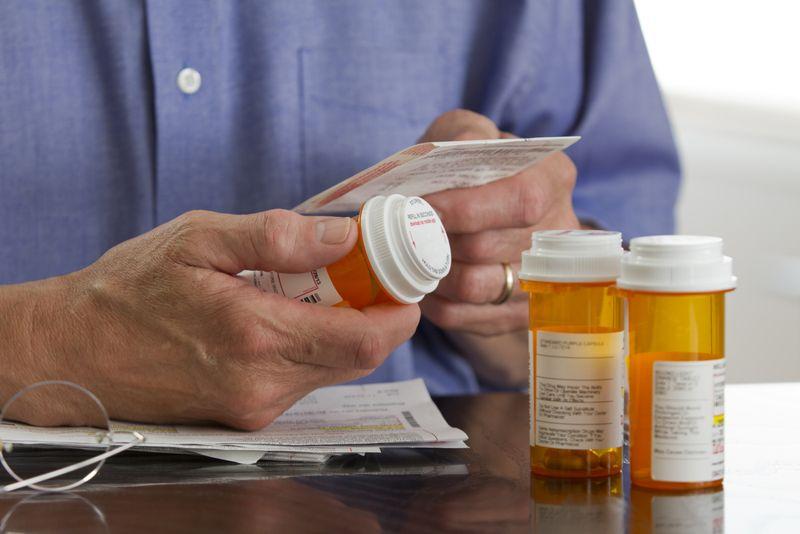 older man reading his prescription bottles