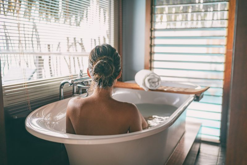 woman soaking in a bath in a bright bathroom