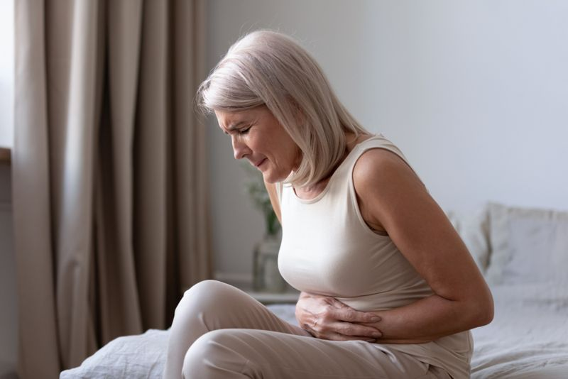 older woman experiencing painful bloating on her bed