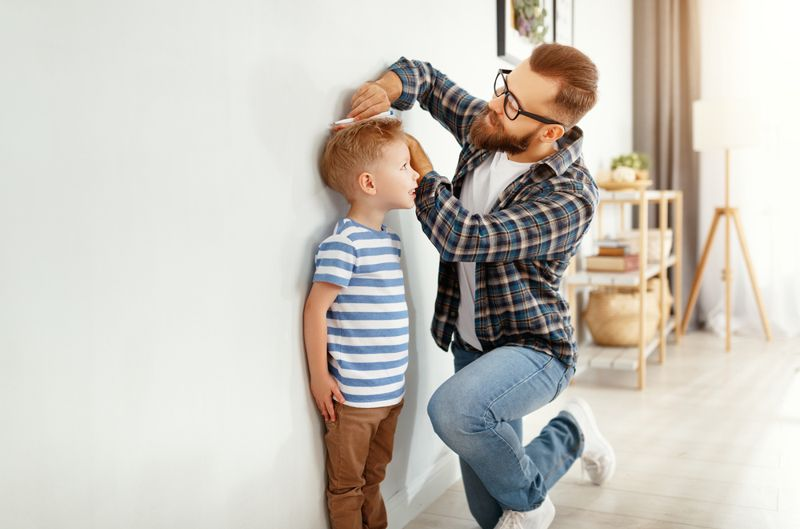 a father measuring his son's height on the wall