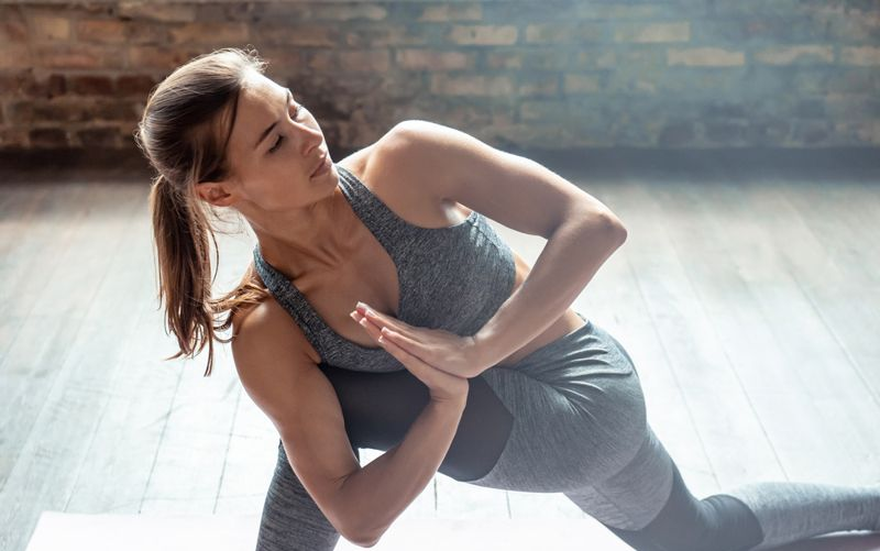 woman in low lunge with twist pose, hip flexor stretch