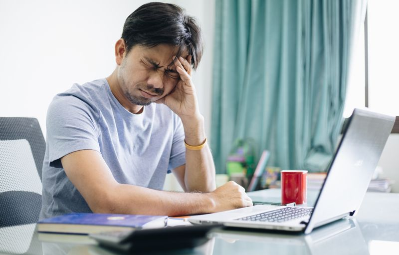 man at his desk with a headache, in pain