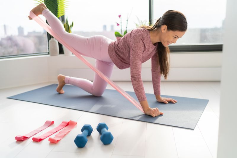 young woman using a resistance band for a workout in her home