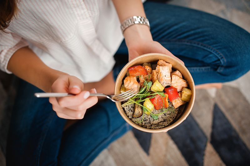 cropped image of a woman eating a healthy bowl meal