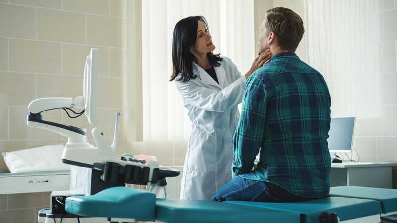 doctor feeling middle aged male patient's throat