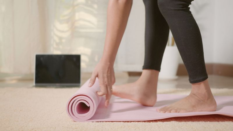 women rolling out her yoga mat