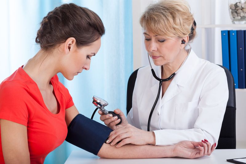 doctor taking patient's blood pressure with cuff and stethoscope