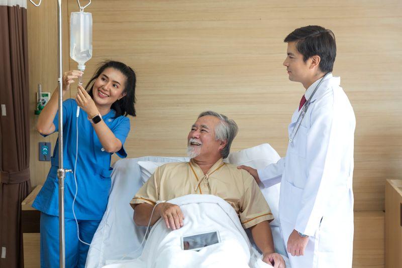 smiling nurse setting up iv fluids for patient in hospital