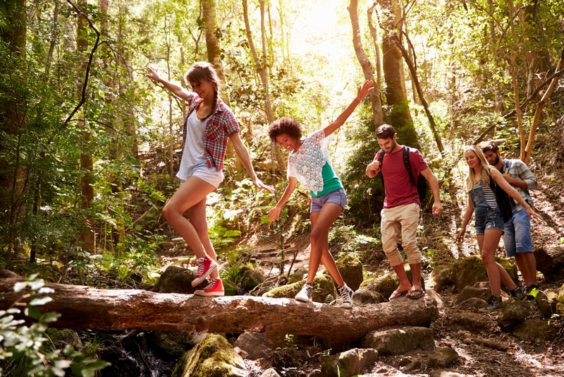 group of young people walking through the forest