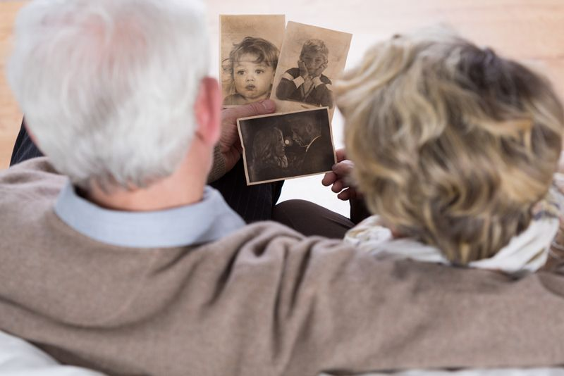 older couple looking at old, sepia photographs