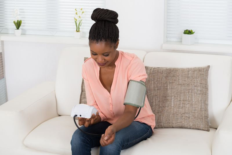 woman taking her blood pressure readings at home