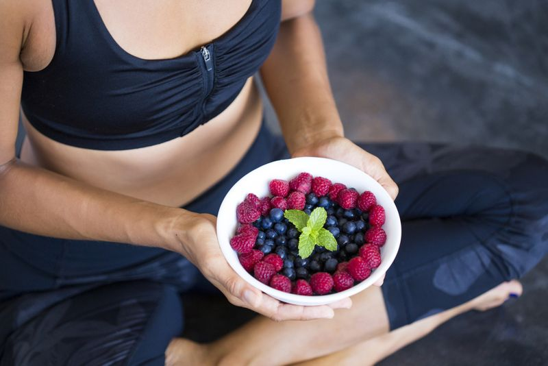 woman in workout clothing holding a bowl of berries